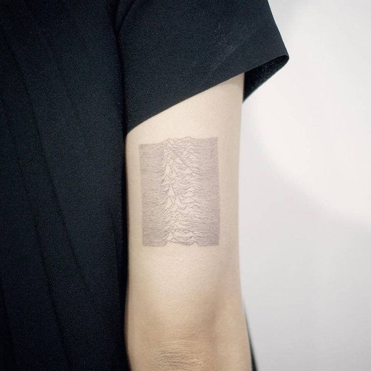 Joy Division's Unknown Pleasures album inspired tattoo on the back of the right arm.