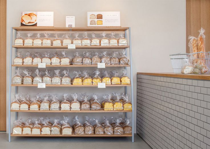Fresh loaves and sugary treats are presented alongside wooden surfaces, ceramic tiles and plants at this bakery in Kiryu, Japan, by SNARK.
