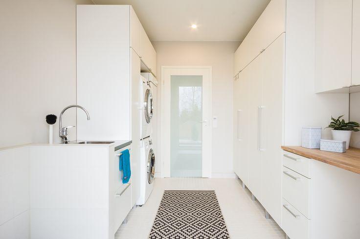 Tilava kodinhoitohuone houkuttelee pyykkäämään. Vaaleat kalusteet