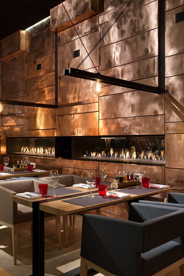 A wall made of copper panels adds shine and texture to the interior of this restaurant.