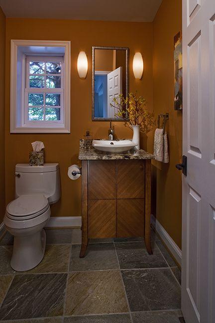 Powder Room Bathroom With Warm Orange Walls And A Wood Vanity
