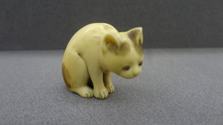 Netsuke. Seated, long-tailed cat. Made of inlaid ivory.