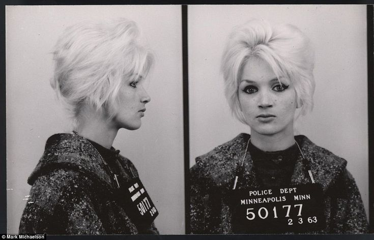 A woman with bleach-blonde hair and a stylish coat is a captured in a mugshot from Minneap...