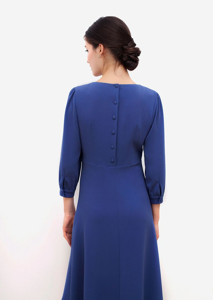 Ellen dress. Charming details enhance the clean cuts and quiet elegance of this timeless, graceful dress. It displays subtle folds and delicate tonal buttons running down the back. The fabric feels soft, free-flowing and light.