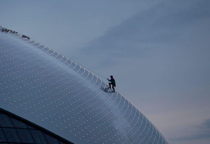 Seorang pekerja memanjat kubah es Bolshoy, arena pertandingan Olimpiade musim dingin, sebagai persiapan menjelang pembukaan Olimpiade di kota Sochi, Rusia. (28 Januari 2014)