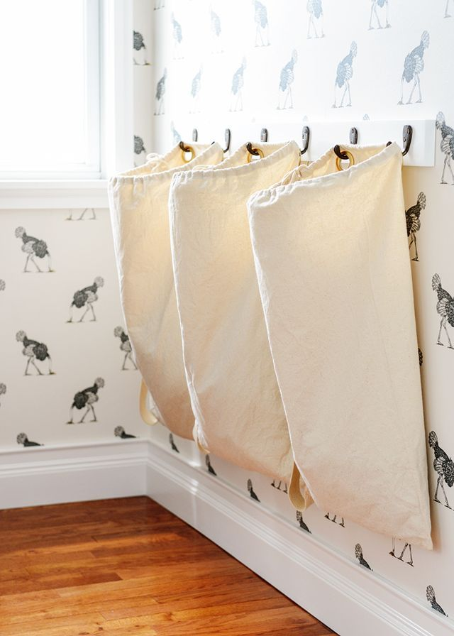wallpaper | laundry bags | hooks | floating vanity | mirror | dipped leg stool  Wanting to see how the laundry room would take shape over the course of its renovation, we waited until the cabinets and