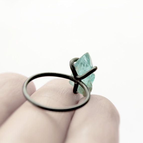 A very simple completely handmade oxidized sterling silver ring. Three thick prongs are holding a raw natural deep blue green apatite stone. The