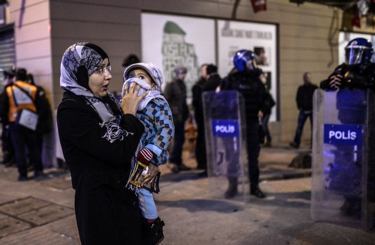 A woman tries to protect her baby from tear gas during clashes between riot-police and prostestors after the funeral of Berkin Elvan, the 15-year-old boy who died from injuries suffered during last year's anti-government protests, in Istanbul on March 12, 2014.