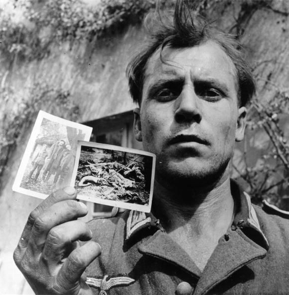 A German officer, captured in Holland, holds up photographs of Dutch civilians hanged and tortured by Nazis. (Photo by Three Lions/Getty Images)