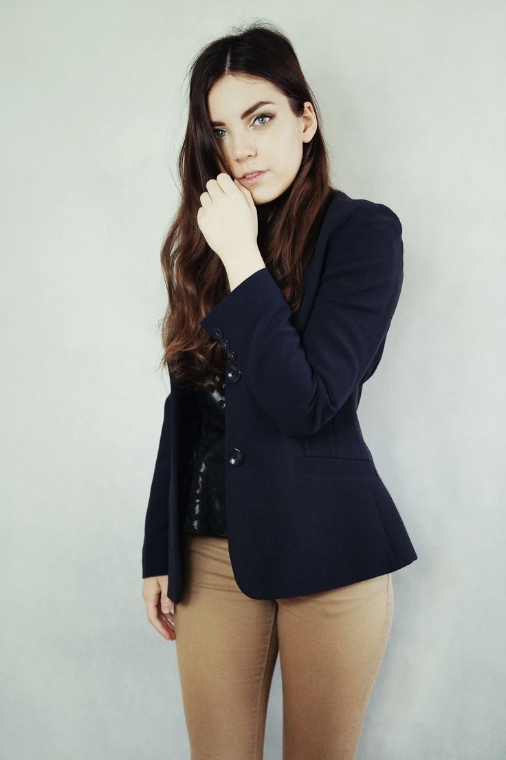 Navy blue jacket and beige trousers. Elegant outfit.
