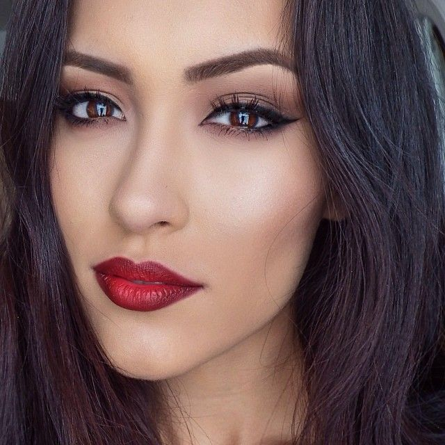 Bold red lip color paired with cat eye.