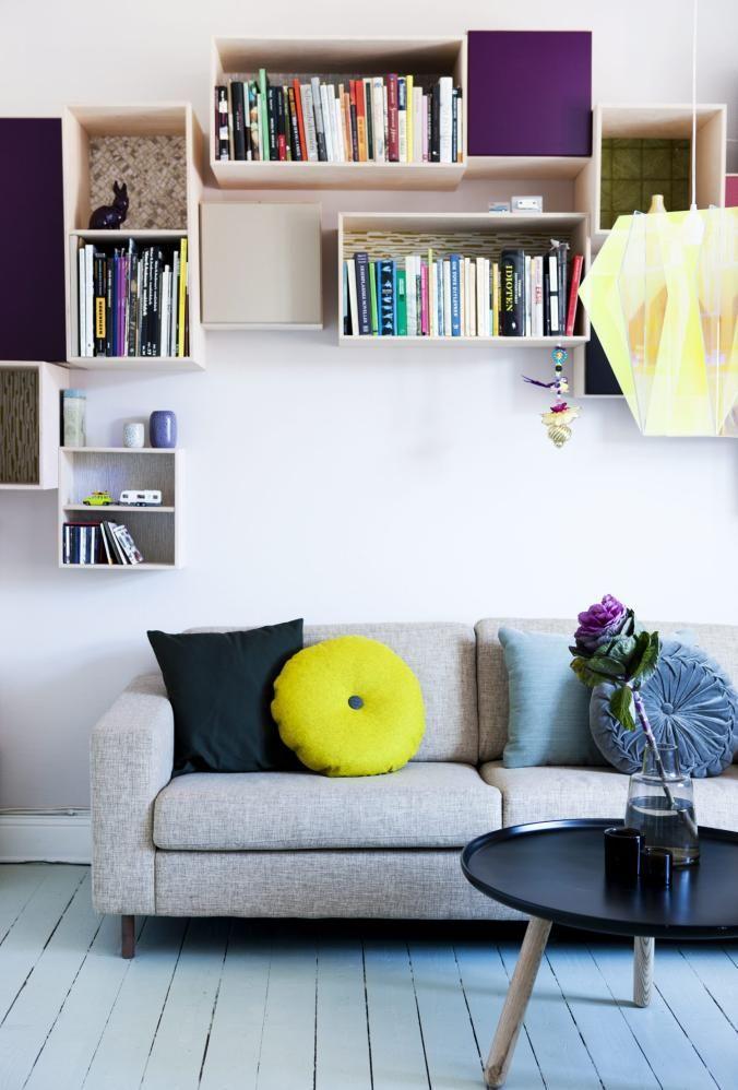 LESEHULE: Beboeren er omgitt av bøker når hun sitter i sofaen. Bokkassene er fra Trævarefabrikkernes Udsalg, traevarer.dk, og er tapetsert med forskjellige retrotapeter inni. Sofaen er fra Bolia, sofabordet fra Normann Copenhagen, lampen fra urbanliving.se. Veggen er malt med lys grå Flutex 5392. Gulvet er malt lyseblått med Flyganol 3503 fra Flügger.