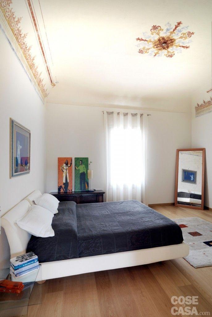 Nella zona notte la camera matrimoniale in stile moderno è arredata con letto tessile e comodini in vetro. Parquet contemporaneo a terra, decorazioni d'epoca a soffitto.