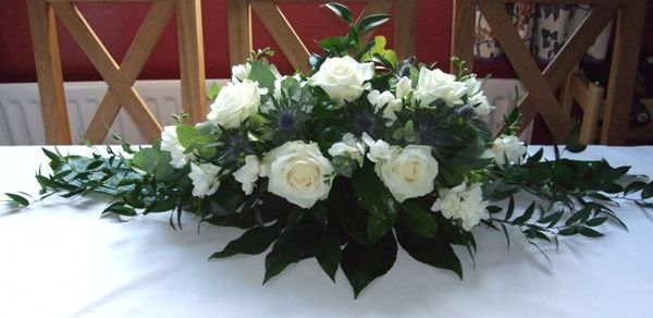 winter wedding flower for head table | Long & low arrangement with ivory roses & thistle