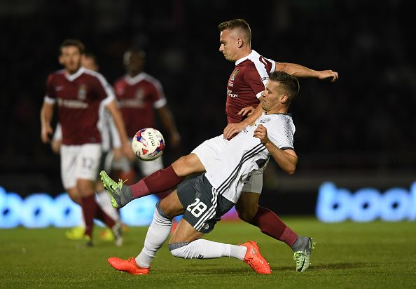 Sam Hoskins of Northampton Town is tackled by Morgan Schneiderlin of Manchester…