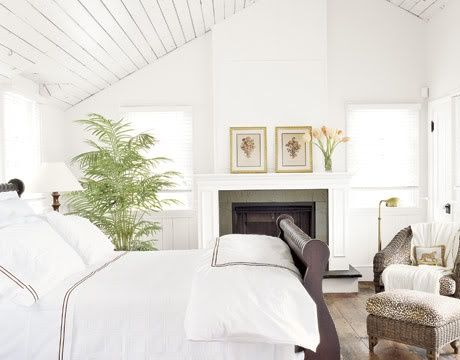 white master bedroom with slanted plank ceiling, and fireplace