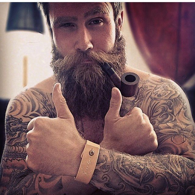 Beard, tattoo, pipe. Thumbs up.