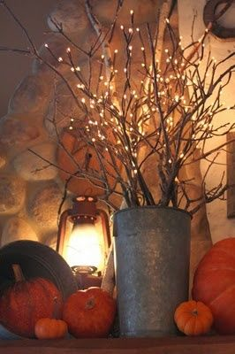 Fall decor- pumpkins, lantern, and lighted branches.