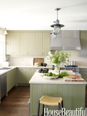 """Soft Green Kitchen: Designer Madeline Stuart concocted a """"modern provincial"""" look with her minimalist update of traditional grooved cabinetry, in a soft custom green with limestone countertops. """"This kitchen needed to be somewhat masculine, but still warm and inviting,"""" she says of the California design. She created a micro-mosaic backsplash for textural interest. The pendants are 1950s Italian."""