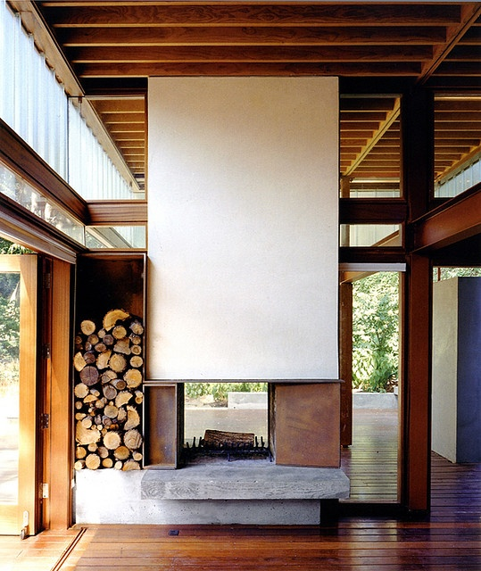 Concrete fireplace. Love the way it's visible from both sides. Cool log storage.