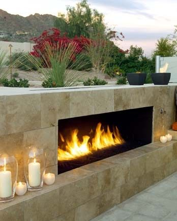 A stone facade gives this outdoor fireplace a natural, but modern look. by Urban Earth Design