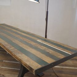 Big handcrafted industrial table, reclaimed wood top and cast iron legs. Loft style. Retro design. Dining room. Restaurant table.