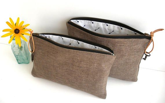 A zipper pouch in dark khaki/light brown linen fabric with black YKK zip. Lined in embroidered arrows fabric and finished with a leather zip pull and small vintage key. Size - about 16.5cm tall by 21.5cm wide (the larger of the 2 pouches in the photo).  A lovely soft linen pouch, with an interesting lining and a very cute vintage key. Great for holding all your bits and bobs - make up, jewellery, sewing or knitting things, handbag stuff, gadgets, first aid items, items needed on a plane ...