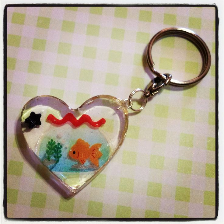 A gold koi, or goldfish in a little red fish bowl in a heart shaped resin keychain to hang all your keys from! A little black candy star sprinkle is also embedded in the resin, and this keychain is approx. 3cm wide and 3cm in length, and 0.5cm thick.    Given the preserving nature of the resin, t...