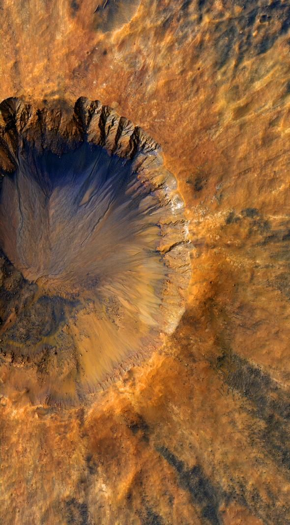 A relatively young Martian crater discolors the red planet's surface like a bruise in this image taken by NASA's HiRISE spacecraft. Researchers can gauge the crater's age thanks to its sharp rim and intact debris field, known as ejecta.