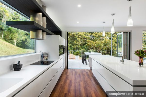 This stunning home is nestled at the bottom of a valley, its kitchen opening into an outdoor area surrounded by beautiful bush land. Imagine hosting a BBQ here!