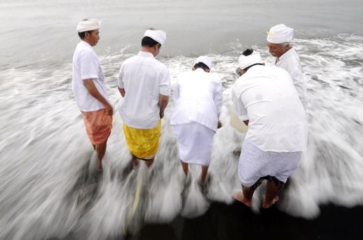 Temple priests taking the water from the sea to be used to wash the sacred artefacts. Photo by Agung Prameswara.