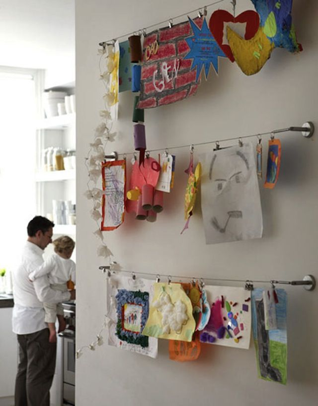 An Ikea curtain wire (Dignitet) and office clips display a collection of children's art. Remodolista: