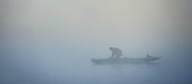 Prague - Czech Republic - Fisherman in mist fog morning river near Charles bridge