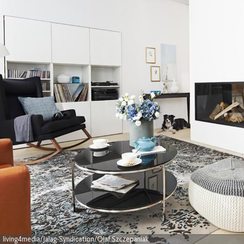 Ideal für kalte Wintertage: Im gemütlichen Schaukelstuhl lässt es sich gut vor dem modernen Kamin entspannen. In diesem Wohnzimmer werden gekonnt moderne  …