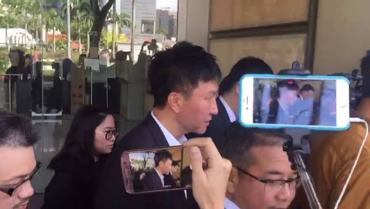 City Harvest Church founder Kong Hee leaving the court after his appeal hearing, surrounded by reporters.