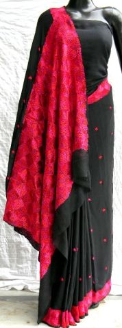 This gorgeous chignon chiffon sari is hand-embroidered in the phulkari/bagh work style. The pallu has heavy, intricate embroidery, with a border running throughout the sari and small motifs at intervals. Blouse piece is attached to the sari. - See more at: http://giftpiper.com/PhulkariWorkChignonChiffonSariBlack-id-249186.html#sthash.o0vn95Cv.dpuf