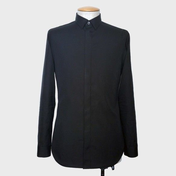 タイトシルエットのフライフロントシャツです。コットン100%のブロード生地はソフトな風合いで肌ざわりも良く、しなやかでわずかな光沢があります。ブラックの生地に黒蝶貝ボタンがシックな印象。細い前立てはフライフロントで衿は小さく、カジュアルコーデならハードなロックスタイルを構築できる。モードなモノトーンコーデやコントラストを強調したスタイルでも活躍できるアイテムです。-----------------------------ブランド:only my red looks vivid作品番号:15003アイテム:メンズシャツカラー:ブラック-----------------------------素材:綿100%-----------------------------Sサイズ:着丈73cm肩幅42.5cm身幅48cm袖丈60.25cmウエスト86cm裾廻94cm-----------------------------