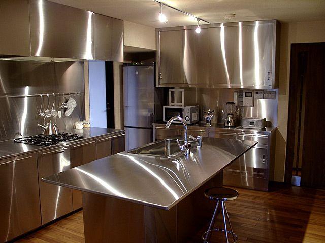 月島の屋形船のキッチンは、オールステンレスでつくられた業務用的な台所です。 築地に程近く、市場で買ってきた魚をさばくことも多いというクライアントのご主人。シンクのあるテーブルを部屋の中央に置いたモダン…