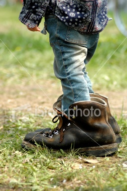 Oversized Boots. A young child tries hard to fill her daddy's shoes.