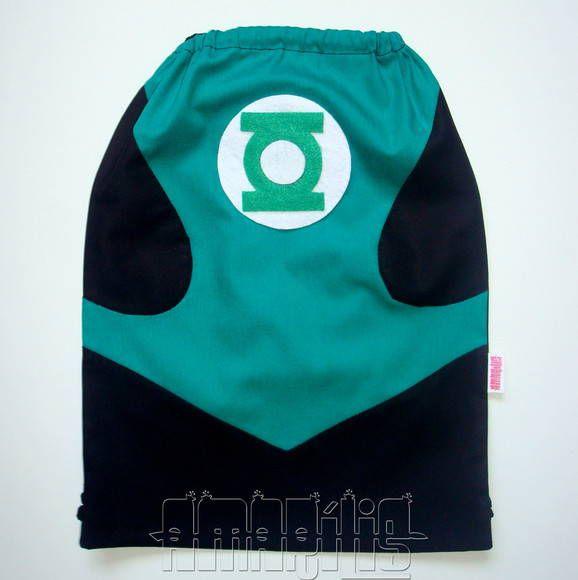 """CRIAÇÃO POR AMARÍLIS ATELIER! <br> <br>Mochila Infantil tipo """"Saquinho"""" com o Modelo Lanterna Verde! <br> <br>Corpo da Mochila em Tecido 100% Algodão. <br>Fechamento Prático! <br> <br>Macacão em Verde e Preto <br>Símbolo do Herói em Feltro <br>Cadarço Preto <br> <br>PEDIDO MÍNIMO: 12 unidades <br>DIMENSÕES: 34 cm x 24 cm"""