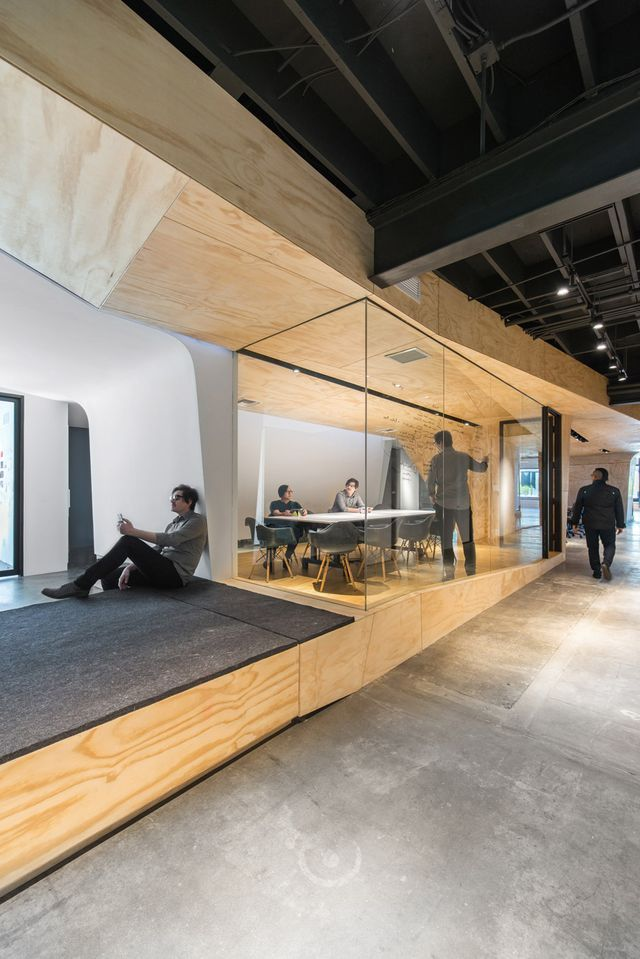 Converted warehouse office by Domaen features sculptural plywood meeting rooms