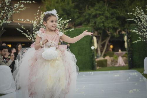 Tulle and feather flower girl dress for walking down the aisle.Las Vegas Wedding Planner Andrea Eppolito designed this luxury wedding at Red Rock Country Club. By Dzign handled the decor shot by wedding photographer Ella Gagiano.