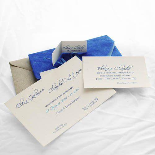 Partecipazione di matrimonio fatta con cartoncino riciclato di colore avorio chiaro. Un lenzuolo di carta di riso avvolge partecipazione e invito al ricevimento. Busta di carta riso 2 colori piegata in stile origami. Nastro di rafia blu  | formato chiuso 11x16cm