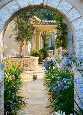 CORFU, GREECE: - MEDITTERANEAN STYLE GARDEN WITH STONE ARCH AND AGAPANTHUS 046797.jpg photo by Clive Nichols