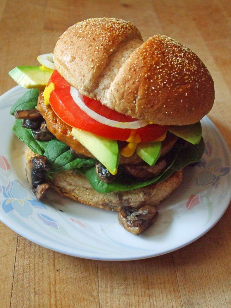veggie burger on a whole wheat bun with spinach, garlic mushrooms, avocado, tomato, onion, sweet chili sauce, and mustard