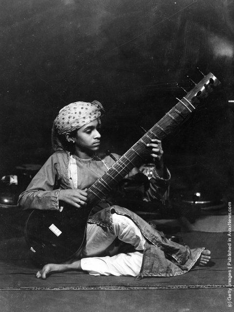 A vina (veena) player in Shan Kar's Company. Basically a large wooden instrument with a resonating bowl, long neck and a second resonating bowl on the underside of the neck. There are two main types, one from southern and one from northern India. (Photo by Sasha/Getty Images). 25th April 1934