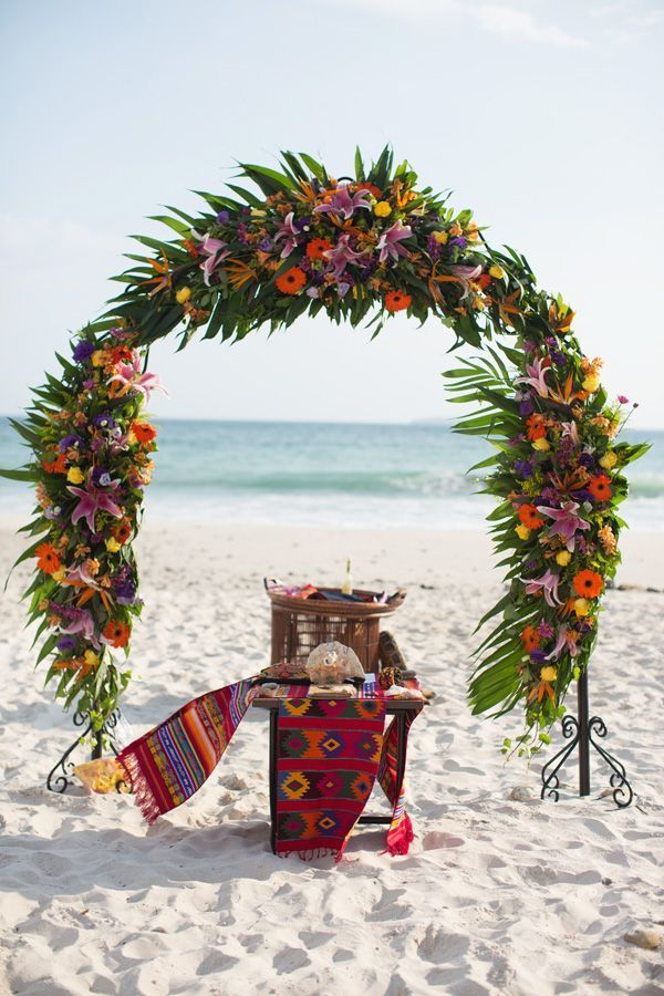 colorful flowers and mexican blankets beach wedding arch