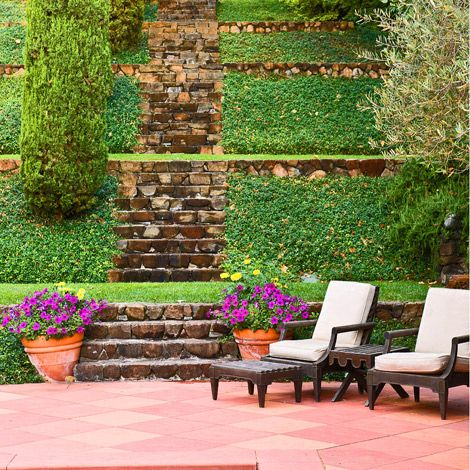 Tiered steps lead down to a pleasant patio at this Napa Valley vineyard - Traditional Home® / Photo: John Granen / Landscape architect: William B. Callaway