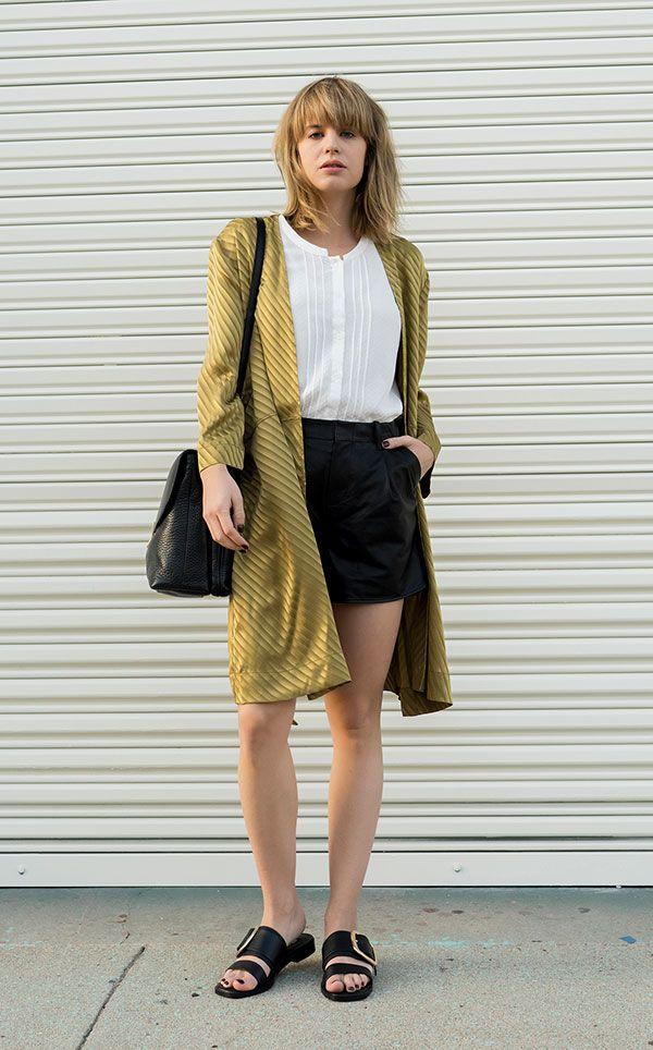 Street style look com blusa branca, shorts couro e maxi casaco verde oliva.