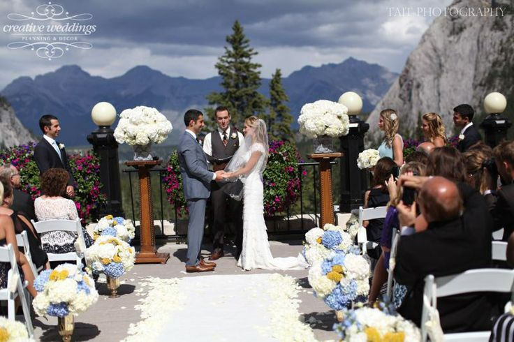 Wedding ceremony on the Outdoor Terrace at the Fairmont Banff Springs; a stunning backdrop of the Canadian Rockies; wedding colors in white, ciel blue and mustard yellow. Decor and design by Creative Weddings Planning & Decor (Photo courtesy of Tait Photography)